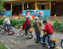 Crianças que conduzem em bicicletas e em 'trotinette's do desenhista em Rússia Foto de Stock