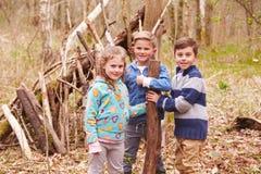 Crianças que constroem o acampamento em Forest Together Imagens de Stock