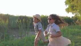 Crianças que correm ao redor no ar livre no campo durante um fim de semana feliz no por do sol filme