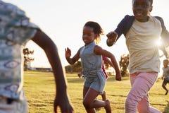 Crianças que correm em um campo aberto, fim da escola primária acima Imagens de Stock