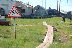 Crianças que cruzam sinal de estrada de advertência na área rural fotos de stock royalty free