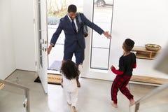 Crianças que cumprimentam e que abraçam a casa de trabalho de As He Returns do pai do homem de negócios do trabalho foto de stock royalty free