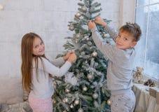 Crianças que decoram a árvore de Natal com bolas Imagens de Stock