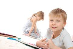 Crianças que desenham e que lêem fotografia de stock