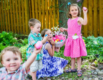 Crianças que encontram ovos em uma caça do ovo da páscoa Foto de Stock