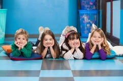Crianças que encontram-se em seguido no assoalho na sala de aula Fotografia de Stock Royalty Free