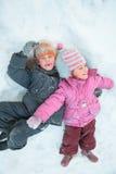 Crianças que encontram-se na neve Fotografia de Stock Royalty Free