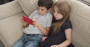 Crianças que encontram-se no sofá com telefone celular vídeos de arquivo