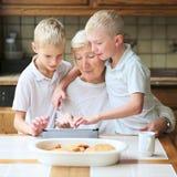 Crianças que ensinam a avó usar o PC da tabuleta Imagens de Stock Royalty Free