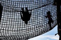 Crianças que escalam dentro de uma elevação da rede da corda no céu - menina que andam e suspensão do menino de cabeça para baixo imagem de stock royalty free