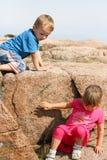 Crianças que escalam para baixo uma rocha Imagens de Stock
