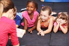 Crianças que escutam o livro do conto de fadas no pré-escolar Fotografia de Stock