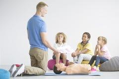 Crianças que escutam o paramédico imagem de stock