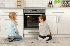 Crianças que esperam a preparação dos bolos no forno imagens de stock