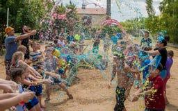 Crianças que espirram com água da cor Festival da água imagens de stock