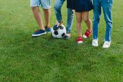 Crianças que estão com a bola de futebol na grama verde Fotos de Stock Royalty Free