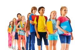 Crianças que estão na linha que guarda livros de texto Fotografia de Stock