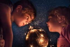 Crianças que exploram o céu noturno com astronomia e descoberta do conceito do planeta das estrelas e da terra do espaço fotografia de stock royalty free