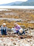 Crianças que exploram a praia Fotos de Stock