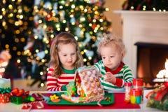 Crianças que fazem a casa do pão do gengibre do Natal Foto de Stock Royalty Free