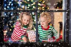 Crianças que fazem a casa do pão do gengibre do Natal Fotos de Stock Royalty Free