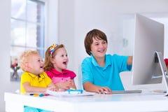 Crianças que fazem trabalhos de casa com computador moderno Fotos de Stock Royalty Free