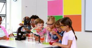 Crianças que fazem uma experiência química no laboratório vídeos de arquivo
