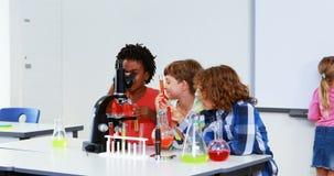 Crianças que fazem uma experiência química no laboratório video estoque