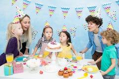Crianças que fundem para fora velas na festa de anos fotos de stock royalty free