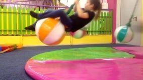 Crianças que giram em um balanço no centro de entretenimento video estoque