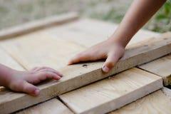 Crianças que guardam as mãos na placa de madeira na oficina Fotografia de Stock Royalty Free