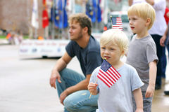 Crianças que guardam bandeiras americanas no evento da parada de Patriotics Imagem de Stock