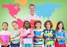 Crianças que guardam livros de escola com o professor na frente do mapa do mundo colorido fotos de stock