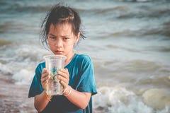 Crianças que guardam o copo plástico que encontrou na praia para acima o conceito limpo ambiental fotos de stock