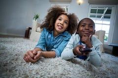 Crianças que guardam o telecontrole ao encontrar-se no assoalho fotos de stock