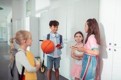 Crianças que guardam seus dispositivos que falam durante a ruptura na escola fotografia de stock royalty free
