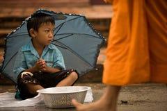Crianças que imploram durante a procissão de monges locais imagens de stock royalty free