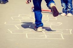 Crianças que jogam amarelinha no campo de jogos fora Imagens de Stock