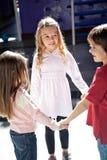 Crianças que jogam ao guardar as mãos no pré-escolar imagem de stock