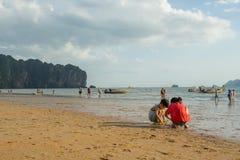 Crianças que jogam a areia e alguns povos que andam e que relaxam na praia do Ao Nang antes do por do sol Fotografia de Stock