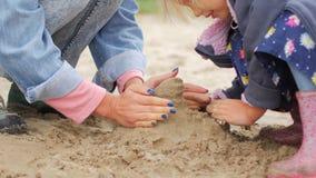 Crianças que jogam a areia na praia A menina constrói o castelo da areia só na praia video estoque