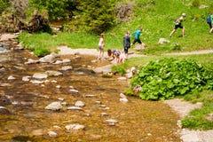 Crianças que jogam com água em um córrego da montanha fotos de stock