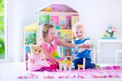 Crianças que jogam com bichos de pelúcia e casa de boneca Imagens de Stock Royalty Free