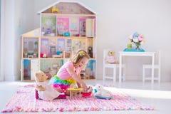 Crianças que jogam com bichos de pelúcia e casa de boneca Imagem de Stock