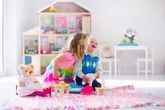 Crianças que jogam com bichos de pelúcia e casa de boneca Imagens de Stock