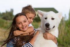 Crianças que jogam com o cão branco do malamute Imagens de Stock Royalty Free