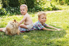 Crianças que jogam com o spitz de Pomeranian do cão Foto de Stock Royalty Free