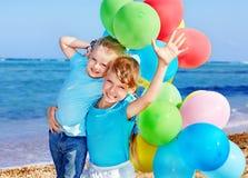 Crianças que jogam com os balões na praia Fotos de Stock Royalty Free