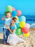 Crianças que jogam com os balões na praia fotos de stock
