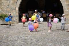 Crianças que jogam com os balões no prefeito da plaza, em Ainsa, Huesca, Espanha em montanhas de Pyrenees, uma cidade murada velh Imagens de Stock
